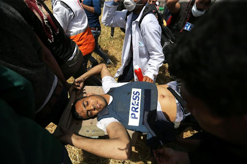 Mortally wounded Palestinian journalist Yasser Murtaja is evacuated during clashes at the Israel-Gaza border on April 6, 2018.