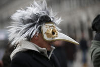"""FILE - In this Jan. 24, 2016 file photo, a man wears a pest doctor mask in St. Mark's Square in Venice, Italy. This carnival mask derives from 16th century doctors wearing beak-nosed masks filled with aromatic herbs to cleanse the air they breathed when treating the sick. Venice's central place in the history of battling pandemics and pestilence will come into focus at this year's Venice Film Festival, which opens Wednesday, Sept. 1, 2021, with the premiere of Pedro Almodovar's in-competition """"Madres Paralelas"""" (Parallel Mothers), which he developed during Spain's 2020 coronavirus lockdown, one of the harshest in the West. (AP Photo/Luca Bruno)"""