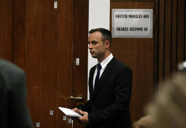Olympic and Paralympic track star Oscar Pistorius walks past the door through which Reeva Steenkamp was shot, at the end of his trial at North Gauteng High Court in Pretoria April 15, 2014.The prosecutor in the murder trial of Pistorius ended his five-day cross-examination of the double amputee track star on Tuesday with a stark summary of how he shot his girlfriend, insisting he killed her deliberately after an argument. REUTERS/Siphiwe Sibeko (SOUTH AFRICA - Tags: SPORT ATHLETICS CRIME LAW)