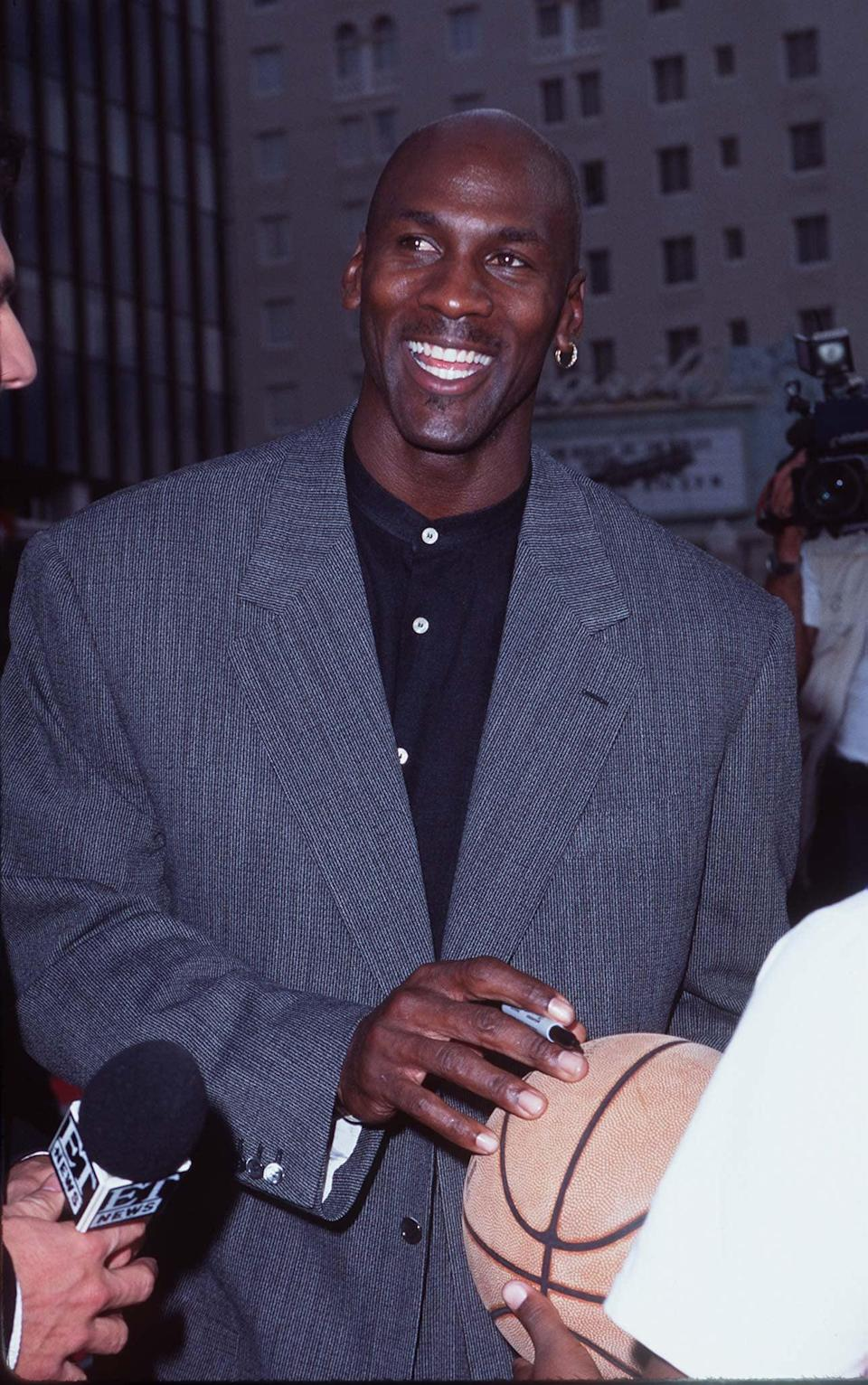 <p>Michael wore a grey blazer with a mandarin-collar button-up shirt and his signature single earring to the premiere of <strong>Space Jam</strong> in Los Angeles in 1996.</p>