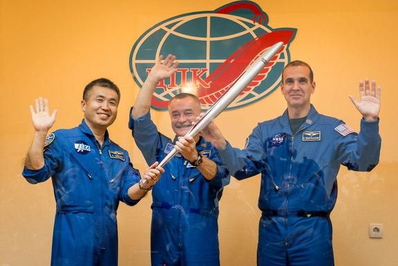 Expedition 38 Flight Engineer Koichi Wakata of the Japan Aerospace Exploration Agency, left, Soyuz Commander Mikhail Tyurin of Roscosmos, and Flight Engineer Rick Mastracchio of NASA, right, smile and wave as they hold an Olympic torch that wil