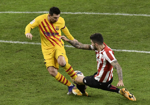 Barcelona's Lionel Messi, left, runs with the ball during the Spanish La Liga soccer match between Athletic Bilbao and Barcelona at San Mames stadium in Bilbao, Spain, Wednesday, Jan. 6, 2021.(AP Photo/Alvaro Barrientos)