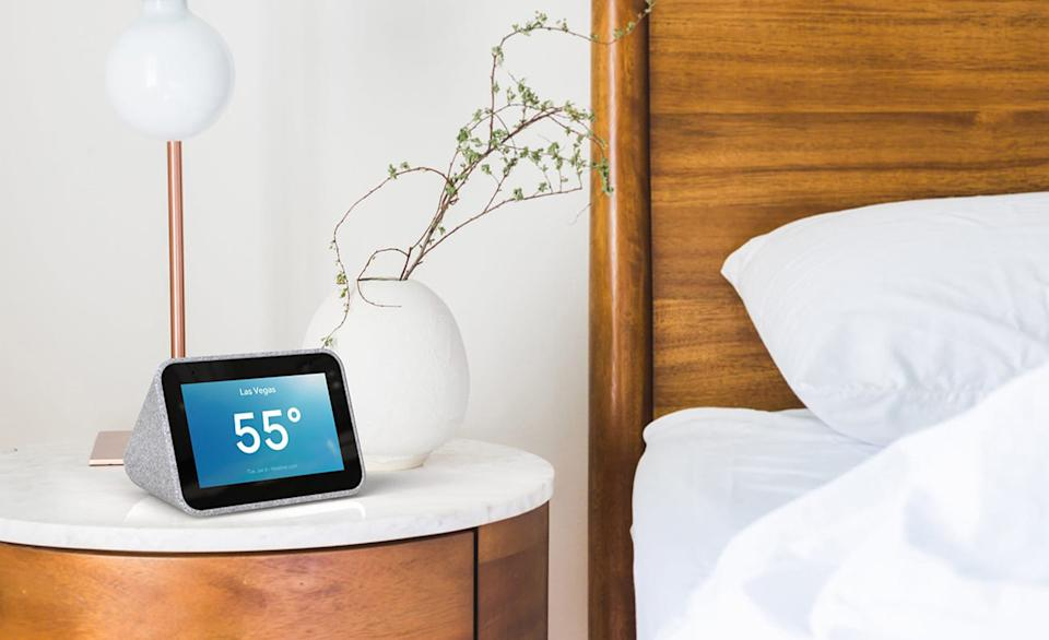 A Lenovo smart clock photographed on a night table next to a bed.