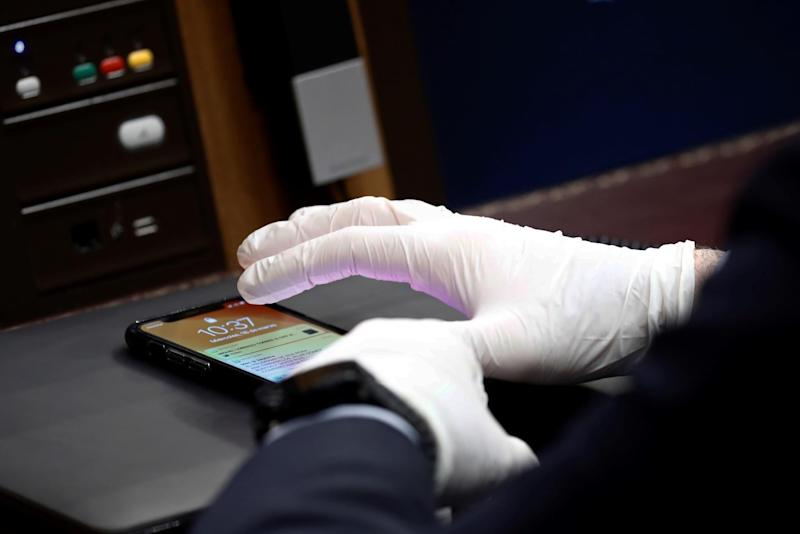 A Member of Parliament using protective gloves uses a smartphone during a session at the Spanish Parliament in Madrid to explain the Government's declaration of a State of Alert and the measures taken to mitigate the coronavirus COVID-19 consequences on March 18, 2020: MARISCAL/POOL/AFP via Getty Images