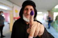 An Iraqi voter shows his inked finger after casting his ballot at a polling station in Baghdad (AFP/Ahmad Al-Rubaye)