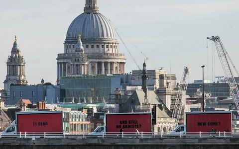 The Community-led organisation, Justice4Grenfell, parades three billboards backdropped by St. Paul's Cathedral - Credit: AP