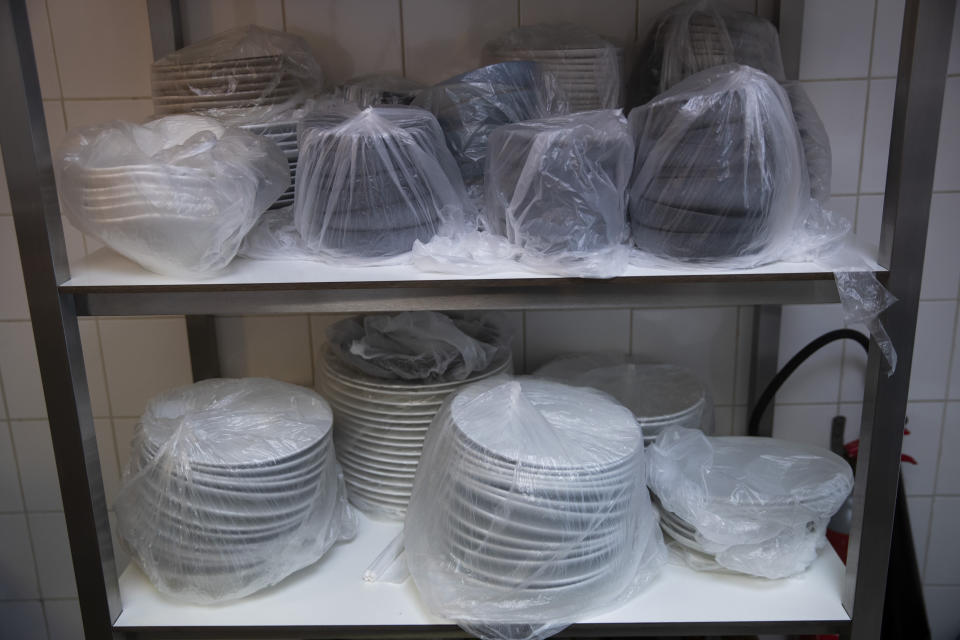 Dinner service plates are covered in plastic and stored away at the restaurant, Tartufo, in Sint-Pieters-Leeuw, Belgium, Thursday, Oct. 22, 2020. Tartufo, a successful dinner restaurant has now been forced to be inventive with take-away service. The coronavirus pandemic is gathering strength again in Europe and, with winter coming, its restaurant industry is struggling. The spring lockdowns were already devastating for many, and now a new set restrictions is dealing a second blow. Some governments have ordered restaurants closed; others have imposed restrictions curtailing how they operate. (AP Photo/Francisco Seco)