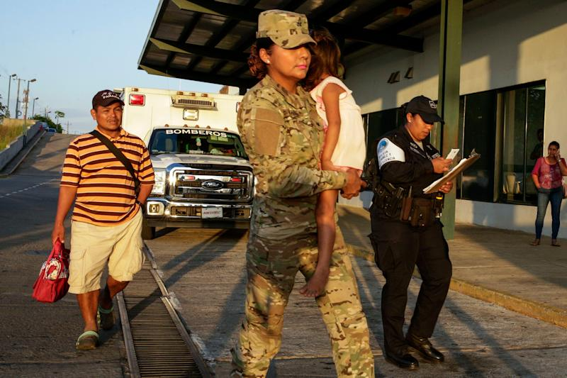 """Jose Gonzalez, left, follows his 5-year-old daughter, carried by a police officer, as they leave a hospital in Santiago, Panama, Jan. 16, 2020. Gonzalez's wife and five of their children are among seven people killed in a religious ritual in the Ngabe Bugle indigenous community. According to local prosecutor Rafael Baloyes indigenous residents were rounded up by lay preachers and tortured, beaten, burned and hacked with machetes to make them """"repent their sins."""""""