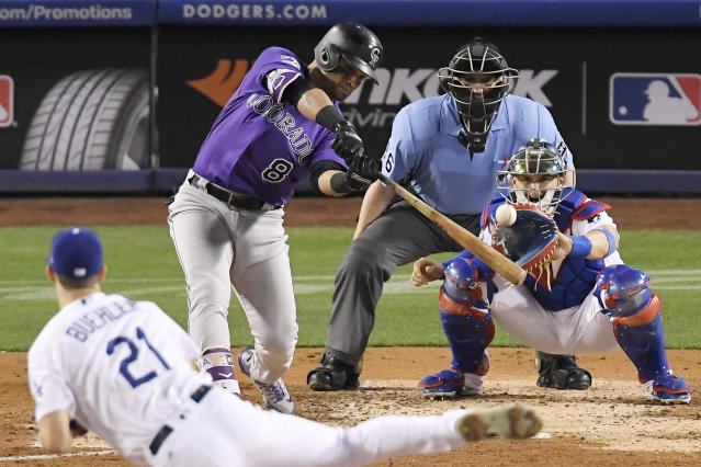Colorado Rockies' Gerardo Parra, second from left, hits a solo home run off Los Angeles Dodgers starting pitcher Walker Buehler during the fifth inning of a baseball game Monday, May 21, 2018, in Los Angeles. Catcher Yasmani Grandal, right, and home plate umpire Ryan Blakney watch. (AP Photo/Mark J. Terrill)