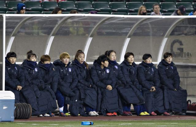 South Korean players bundle up on the bench during the first half of an international friendly soccer match against Canada, Wednesday, Oct. 30, 2013, in Edmonton, Alberta. (AP Photo/The Canadian Press, Jason Franson)
