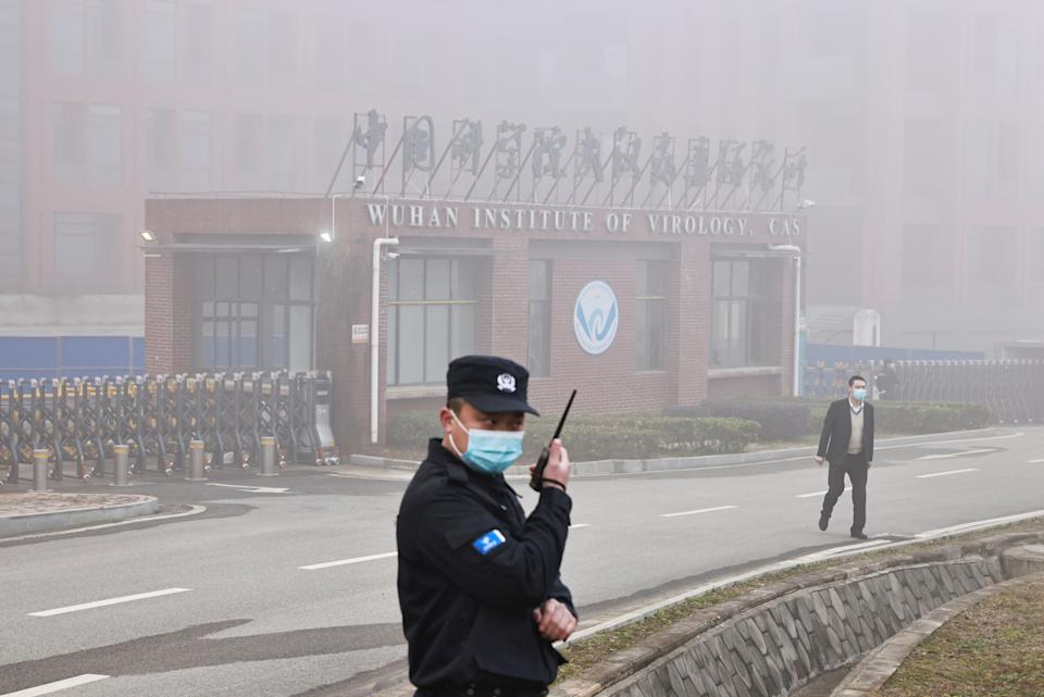 Security personnel stand outside Wuhan Institute of Virology as members of the World Health Organisation team tasked with investigating the origins of the coronavirus disease arrive for a visit, in Wuhan, Hubei province, China on February 3, 2021.