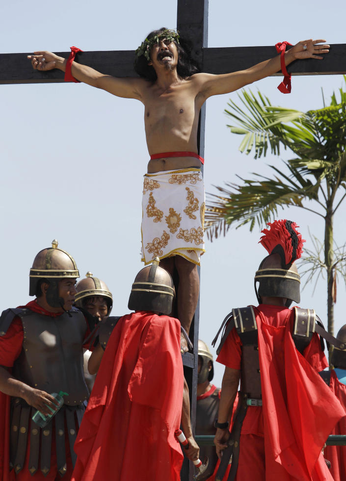 A Filipino penitent shouts as his hands and feet are nailed to the cross during Good Friday rituals on March 29, 2013 at Cutud, Pampanga province, northern Philippines. Several Filipino devotees had themselves nailed to crosses Friday to remember Jesus Christ's suffering and death, an annual rite rejected by church leaders in this predominantly Roman Catholic country. (AP Photo/Aaron Favila)