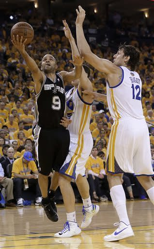San Antonio Spurs guard Tony Parker (9) shoots against Golden State Warriors center Andrew Bogut (12) and guard Klay Thompson (11) during the second quarter of Game 3 of a Western Conference semifinal NBA basketball playoff series in Oakland, Calif., Friday, May 10, 2013. (AP Photo/Jeff Chiu)