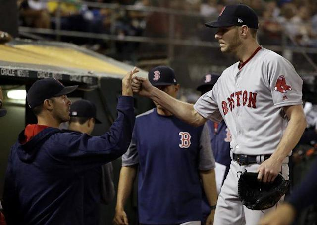 Boston Red Sox starting pitcher Chris Sale (R) is greeted at the dugout after recording his tenth and final strikeout against the A's on Friday, May 19. (AP)