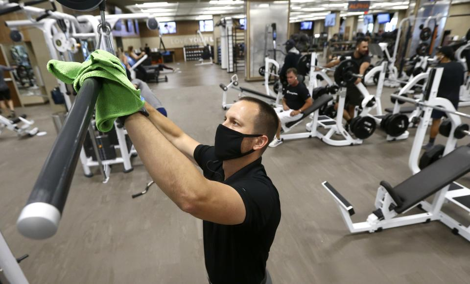 Jason Nichols, facilities operation manager at Life Time, disinfects equipment at the Life Time Biltmore as it opens for business after being closed due to the coronavirus Monday, May 18, 2020, in Phoenix. (AP Photo/Ross D. Franklin)