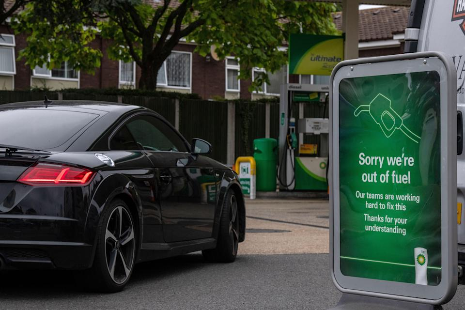 A car drives past a sign informing customers that they are out of fuel at a BP garage on Sunday in Grove Park, London (Getty)