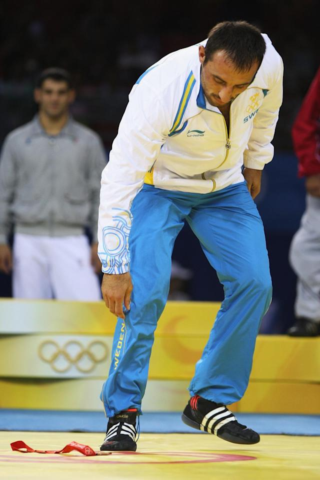 Ara Abrahamian of Sweden leaves the podium immediatley after receiving the bronze medal he won in the Men's Greco-Roman 84kg category and discards it in the center of the mat at the China Agriculture University Gymnasium during Day 6 of the Beijing 2008 Olympic Games on August 14, 2008 in Beijing, China. (Photo by Ezra Shaw/Getty Images)