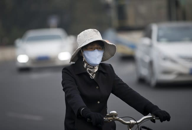 A woman wearing a face mask bicycles on a road in Beijing Tuesday, Oct. 22, 2013. Beijing is seeking to tame its smog emergencies by preparing emergency measures such as factory shutdowns and traffic limits to kick in when air pollution levels are high. (AP Photo/Andy Wong)