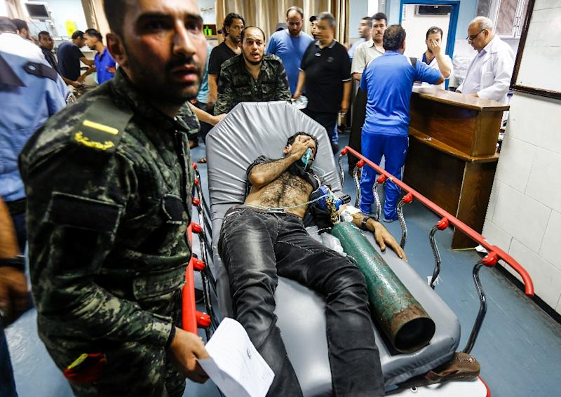 Members of Hamas' military police bring in an Palestinian injured by Israeli air strikes to receive medical attention at al-Shifa hospital in Gaza City on July 14, 2018 (AFP Photo/ANAS BABA)