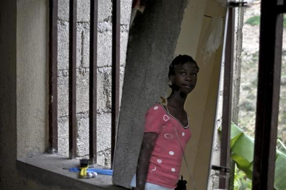 Haitian girl Fabien Destine, 14, who suffers from VSP congenital heart disease, or a hole in the chamber wall, is reflected in a mirror at her home in Port-au-Prince, March 24, 2012.
