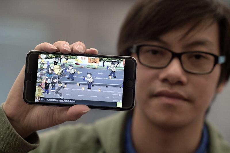 Mobile phone app designer Fung Kam-keung, CEO and founder of Awesapp Limited, holds a smartphone with one of his latest games, 'Yellow Umbrella', seen at the Awesapp Ltd. office in Hong Kong, on October 23, 2014 (AFP Photo/Nicolas Asfouri)