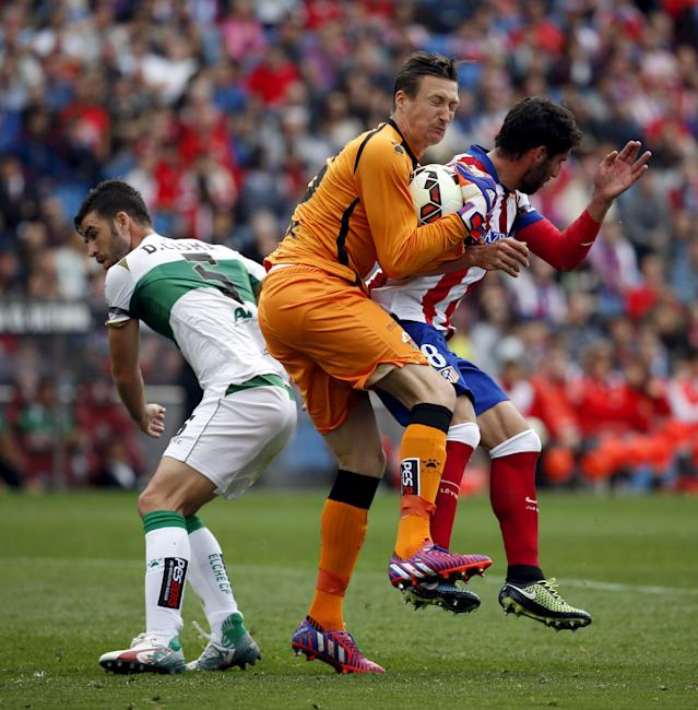 Atletico Madrid's Raul Garcia (R) clashes with Elche's goalkeeper Przemyslaw Tyton (C) during their Spanish first division soccer match at Vicente Calderon stadium in Madrid, April 25, 2015. REUTERS/Susana Vera
