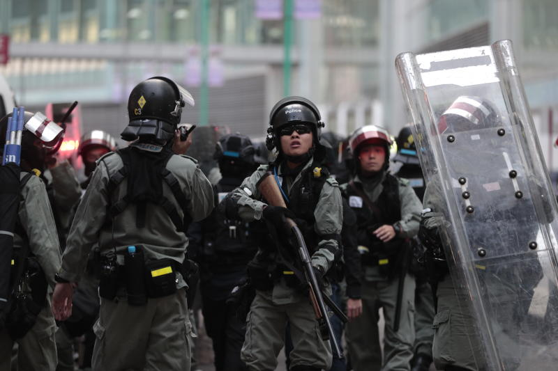 Riot police take defensive position after an object was thrown at them in Hong Kong, Sunday, Nov. 10, 2019. Protesters smashed windows in a subway station and a shopping mall Sunday and police made arrests in areas across Hong Kong amid anger over a demonstrator's death and the arrest of pro-democracy lawmakers.Hong Kong is in the sixth month of protests that began in June over a proposed extradition law and have expanded to include demands for greater democracy and other grievances. (AP Photo/Dita Alangkara)