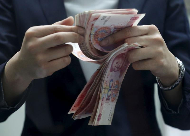 A clerk counts Chinese 100 yuan banknotes at a branch of a foreign bank in Beijing