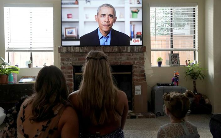 Torrey Pines High School graduating student Phoebe Seip, 18 (centre), and her sisters Sydney, 22, and Paisley, 6, watch Barack Obama deliver a virtual commencement address to millions of high school seniors - REUTERS/Bing Guan