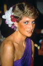 <p>During a visit to Thailand in 1986, Princess Diana adopted a swept-back look finished with an assortment of flowers. She also adopted striking blue eyeliner to accompany her one-shouldered dress.<br><em>[Photo: PA]</em> </p>