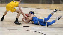 UCLA guard Jaime Jaquez Jr. battles for a loose ball with Michigan guard Franz Wagner (21) during the first half of an Elite 8 game in the NCAA men's college basketball tournament at Lucas Oil Stadium, Tuesday, March 30, 2021, in Indianapolis. (AP Photo/Michael Conroy)