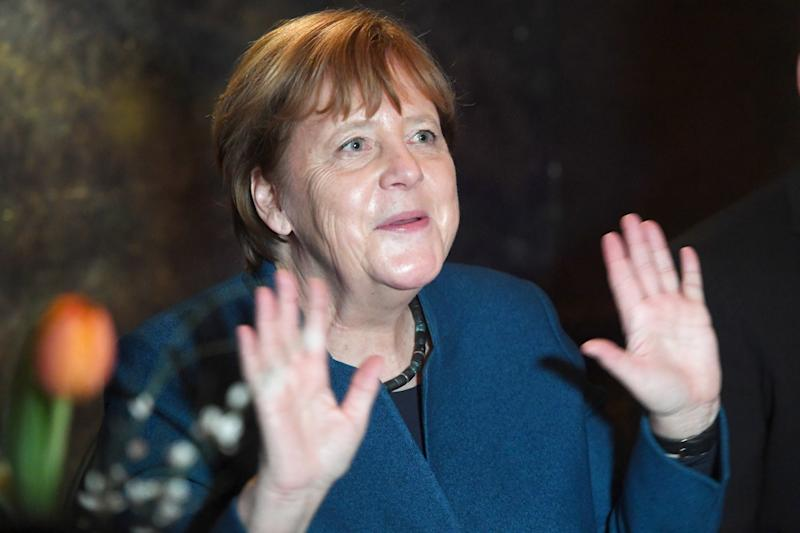 28 February 2020, Mecklenburg-Western Pomerania, Stralsund: Chancellor Angela Merkel (CDU) raises both hands up at the annual reception of her constituency to show that she does not want to shake hands with anyone because of a possible risk of infection by the corona virus. Merkel has represented the constituency of Stralsund-Greifswald-Rügen-Vorpommern with a direct mandate in the Bundestag since 1990. Photo: Stefan Sauer/dpa (Photo by Stefan Sauer/picture alliance via Getty Images)