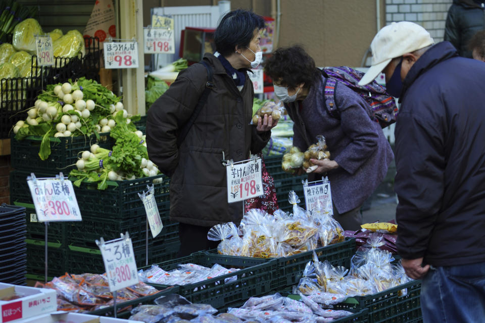 People wearing protective masks to help curb the spread of the coronavirus shop at a vegetable shop in Tokyo Thursday, Jan. 14, 2021. The Japanese capital confirmed more than 1500 new coronavirus cases on Thursday. (AP Photo/Eugene Hoshiko)