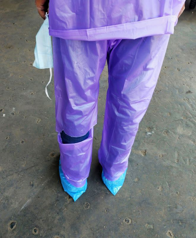 A doctor wearing a torn raincoat stands at the major coronavirus disease (COVID-19) treatment facility in Kolkata