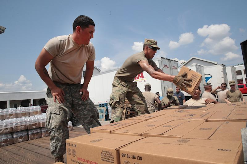 Members of the Texas Army National Guard from El Paso, Texas distribute food and water to flood victims in Orange, Texas, (Scott Olson via Getty Images)