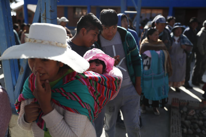 A woman carries her child on her back as she stands in line to vote at a polling station during general elections in La Paz outskirts, Bolivia, Sunday, Oct. 20, 2019. Bolivians are voting in general elections Sunday where President Evo Morales is Presidential candidate for a fourth term. (AP Photo/Jorge Saenz)