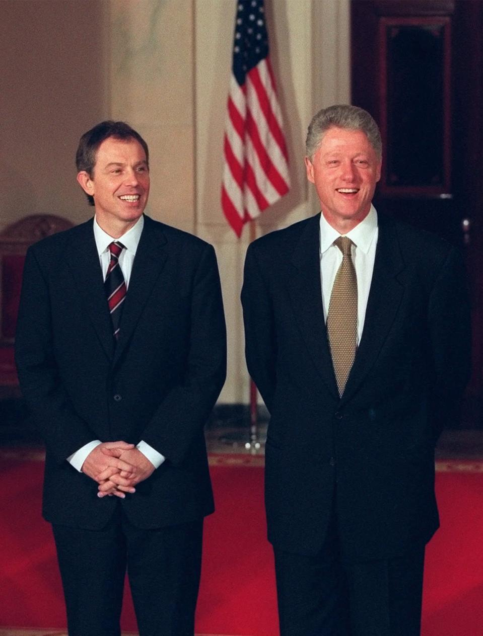 """FILE - In this Feb. 5, 1998, file photo President Bill Clinton, right, and British Prime Minister Tony Blair stand during a welcoming ceremony for Blair at the White House in Washington. On Feb. 6, 1988, during a Clinton news conference he was asked at what point he might decide the crisis was too much to put his family through anymore and resign. """"Never,"""" he said, stone-faced. (AP Photo/J. Scott Applewhite, File)"""