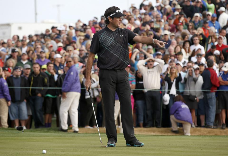 Bubba Watson talks to his caddie after missing a short putt on the 18th hole that would have forced a playoff during the final round of the Phoenix Open golf tournament on Sunday, Feb. 2, 2014, in Scottsdale, Ariz. Watson's missed putt allowed Kevin Stadler to earn the win. (AP Photo/Ross D. Franklin)