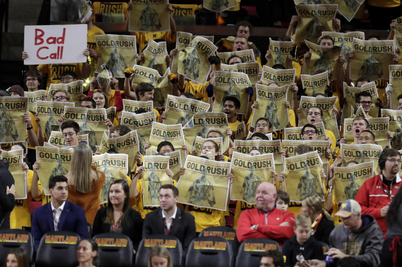Students hold newspapers prior to an NCAA college basketball game between Maryland and Illinois, Saturday, Dec. 7, 2019, in College Park, Md. (AP Photo/Julio Cortez)