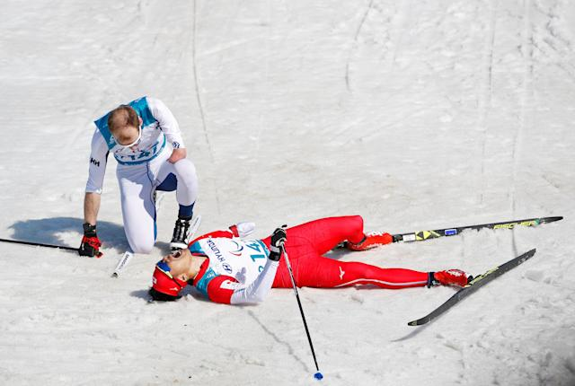 Cross-Country Skiing - Pyeongchang 2018 Winter Paralympics - Men's 1.5km Sprint Classic - Standing - Final - Alpensia Biathlon Centre - Pyeongchang, South Korea - March 14, 2018 - Yoshihiro Nitta of Japan collapses in the snow after winning silver, next to Ilkka Tuomisto of Finland. REUTERS/Carl Recine