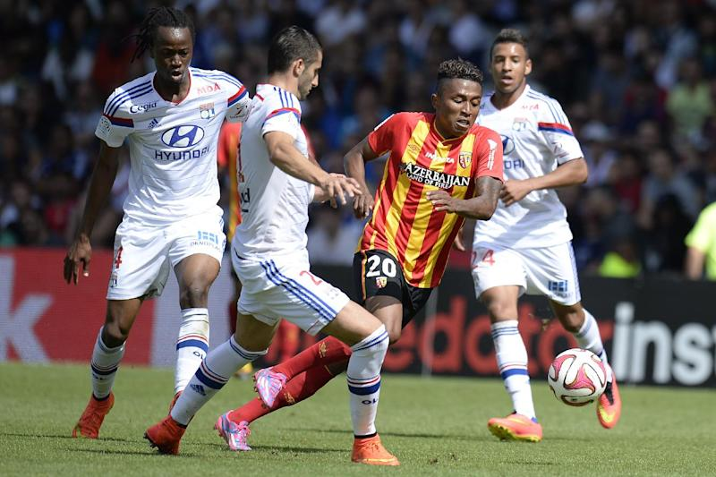 Lens' midfielder Lalaina Nomenjanahary (2nd R) vies for the ball with Lyon's midfielder Maxime Gonalons (2nd L) and defender Bakary Kone (L) on August 24, 2014 (AFP Photo/Romain Lafabrugue )