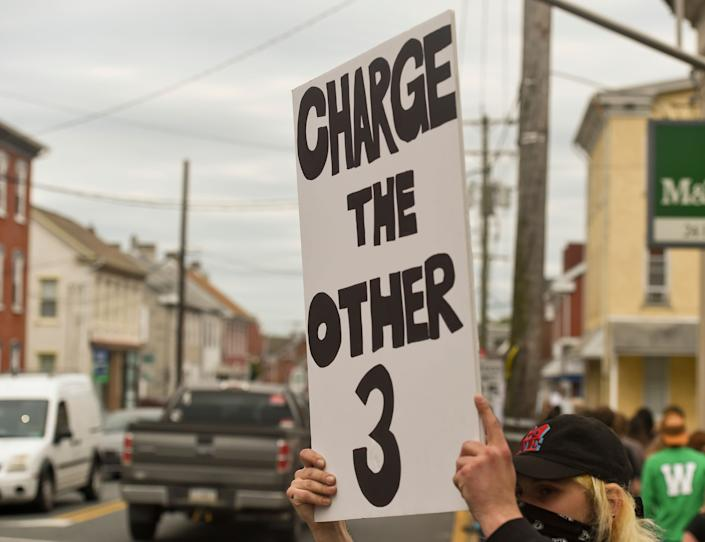 """<i>In Boyertown, Pennsylvania, a protester holds a sign that says """"Charge the other 3,"""" referring to the other three police officers present when their colleague kneeled on George Floyd's neck and killed him. The former officers have <a href=""""https://www.huffpost.com/entry/3-cops-charged-george-floyd-death_n_5ed15c7cc5b63f2b5793fa50"""" data-ylk=""""slk:since been charged"""" class=""""link rapid-noclick-resp"""">since been charged</a> with aiding and abetting.</i>"""