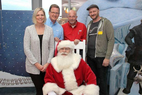 PHOTO: Mark Miller, center, in red, poses with Santa Claus and other parents and officials at Children's of Alabama. (Mike Strawn/Children's of Alabama )