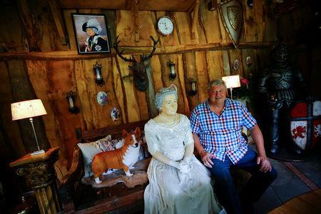 """Gary Blackburn, a 53-year-old tree surgeon from Lincolnshire, Britain, poses with a life-seize model of Queen Elizabeth and a corgi dog mock-up at """"Robin Hood's hut"""" of his British curiosities collection called """"Little Britain"""" in Linz-Kretzhaus, south of Germany's former capital Bonn, Germany, August 24, 2017. REUTERS/Wolfgang Rattay"""