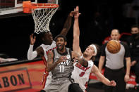 Brooklyn Nets guard Kyrie Irving (11) loses the ball driving to the basket past Miami Heat forward Kelly Olynyk (9) during the first half of an NBA basketball game Monday, Jan. 25, 2021, in New York. (AP Photo/Adam Hunger)
