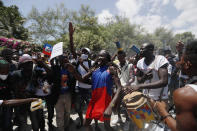 Supporters of former Haitian President Jean-Bertrand Aristide celebrate as they wait at the airport for his expected arrival from Cuba, where he underwent medical treatment, in Port-au-Prince, Haiti, Friday, July 16, 2021. Aristide's return adds a potentially volatile element to an already tense situation in a country facing a power vacuum following the July 7 assassination of President Jovenel Moïse. (AP Photo/Fernando Llano)