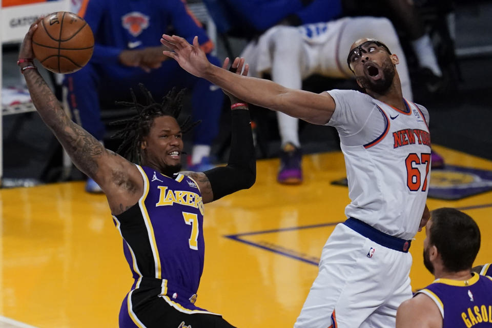 Los Angeles Lakers guard Ben McLemore (7) catches a rebound against New York Knicks center Taj Gibson (67) during the second quarter of a basketball game Tuesday, May 11, 2021, in Los Angeles. (AP Photo/Ashley Landis)