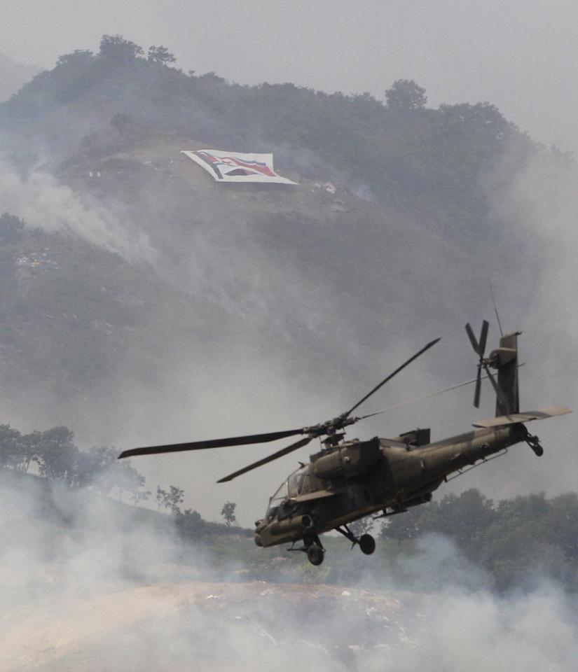 In this photo taken Tuesday, June 19, 2012, a U.S. AH-64 Apache helicopter flies near the North Korean flag during South Korea-U.S. joint military live-fire drills at Seungjin Fire Training Field in Pocheon, South Korea, near the border with the North Korea. The drills were held in a show of combat readiness ahead of the 62nd anniversary of the start of the Korean War on June 25. (AP Photo/Lee Jin-man)