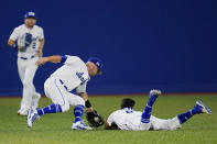 Israel's Scott Burcham, right, dives and cannot reach a ball picked up by Rob Paller, center, as Blake Gailen (2) looks on during a baseball game against the United States at the 2020 Summer Olympics, Friday, July 30, 2021, in Yokohama, Japan. (AP Photo/Sue Ogrocki)
