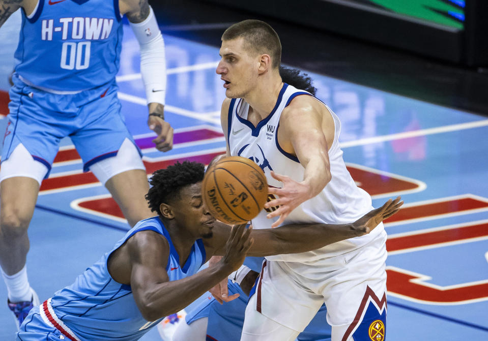 Denver Nuggets center Nikola Jokic (15) passes to a teammate while being defended by Houston Rockets forward Jae'Sean Tate (8) and guard Kevin Porter Jr. (3) during the third quarter of an NBA basketball game Friday, April 16, 2021, in Houston. (Mark Mulligan/Houston Chronicle via AP)